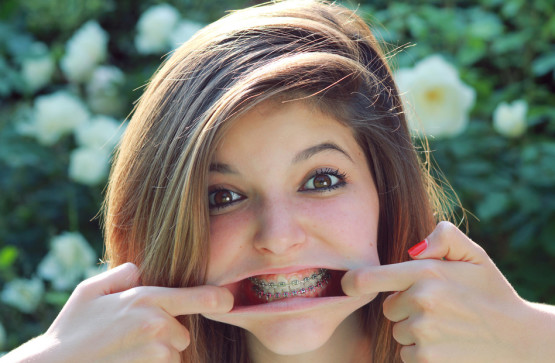 Young pretty teenager with funny expression , showing her braces .